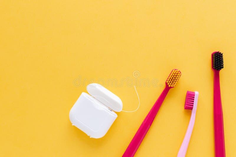 Igiene dentale - spazzolini da denti, disposizione piana del filo per i denti, vista superiore, spazio della copia, fondo giallo immagini stock