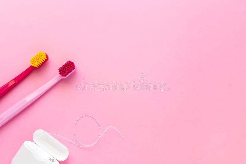 Igiene dentale - spazzolini da denti, disposizione piana del filo per i denti, vista superiore, spazio della copia, fondo rosa fotografia stock