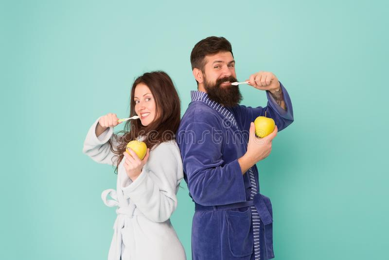 Igiene orale Gli accappatoi delle coppie tengono gli spazzolini da denti e le mele L'igiene personale Coppie in denti di pulizia  immagini stock libere da diritti