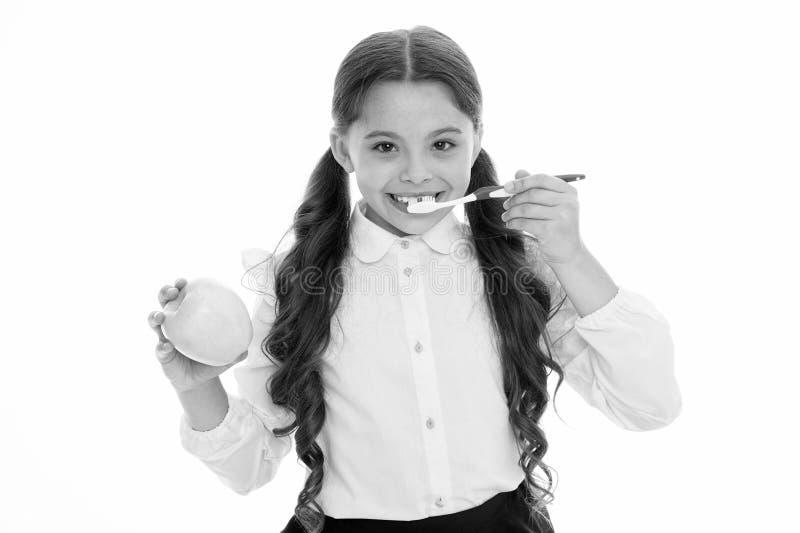 Igiene orale Spazzolino da denti delle tenute della ragazza e fondo svegli di bianco della mela La ragazza del bambino tiene il d fotografia stock libera da diritti