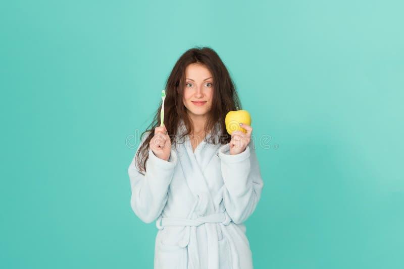 Igiene orale Spazzolino da denti e mela della tenuta dell'accappatoio della donna L'igiene personale Pulisca i denti, il filo di  immagini stock