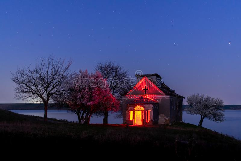Iglesia abandonada y nightscape floreciente de los ?rboles fotografía de archivo libre de regalías