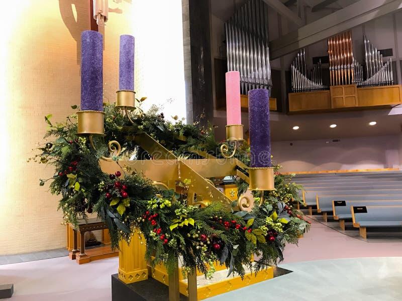 Iglesia Advent Wreath con las bayas violetas de la vela y el soporte púrpuras y color de rosa del oro imagen de archivo libre de regalías