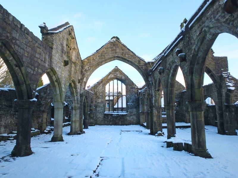 Iglesia arruinada medieval en el heptonstall cubierto en la nieve que muestra arcos y columnas contra un cielo azul del invierno imágenes de archivo libres de regalías