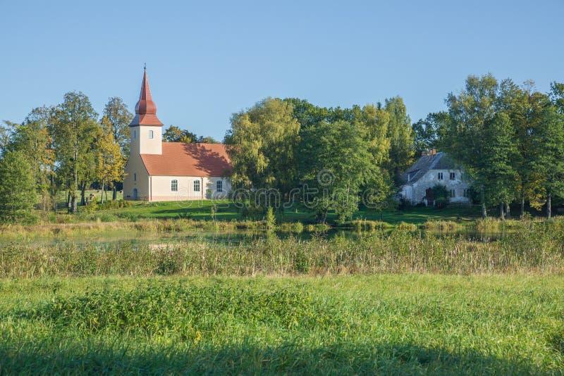 Iglesia cerca del lago, Araisi, Letonia Naturaleza y edificio foto de archivo