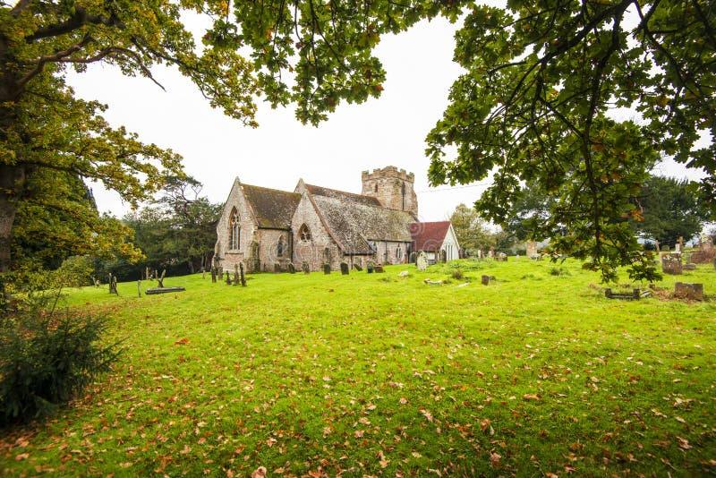 Iglesia de Crowhurst, al noroeste de Hastings, de Sussex del este, Inglaterra - casera a algún tejo, acebo y robles antiguos imágenes de archivo libres de regalías