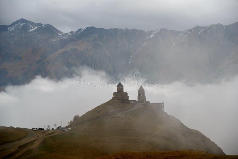 Iglesia de la trinidad de Gergeti en nubes fotografía de archivo