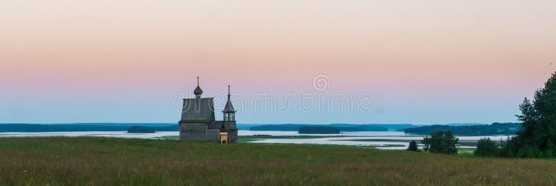 Iglesia de madera en el top de la colina Opinión de la puesta del sol del pueblo de Vershinino Región de Arkhangelsk, Rusia septe imagenes de archivo