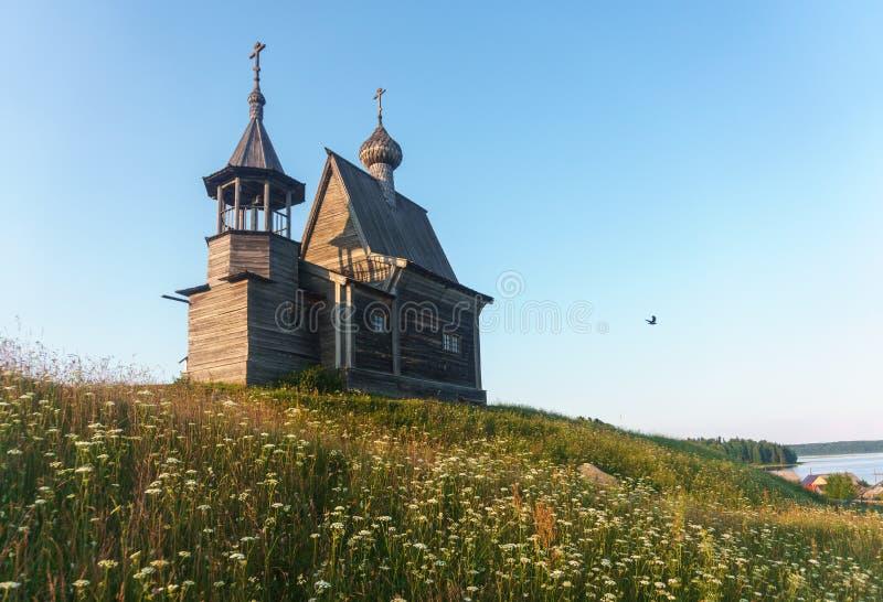 Iglesia de madera en el top de la colina Opinión de la puesta del sol del pueblo de Vershinino Región de Arkhangelsk, Rusia septe imagen de archivo libre de regalías