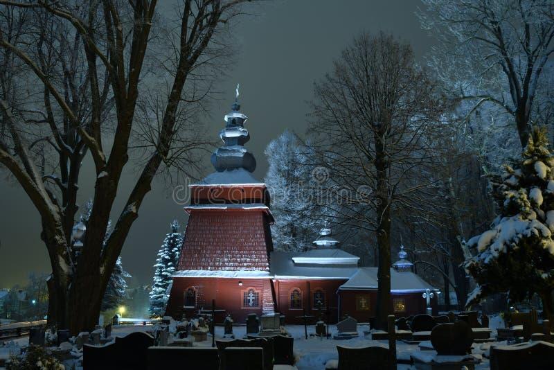 Iglesia de madera iluminada hermosa en invierno por completo de la nieve Tylicz Polonia fotos de archivo