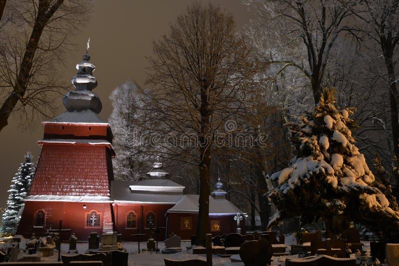 Iglesia de madera iluminada hermosa en invierno por completo de la nieve Tylicz Polonia fotografía de archivo libre de regalías