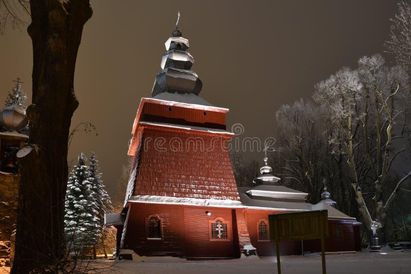 Iglesia de madera iluminada hermosa en invierno por completo de la nieve Tylicz Polonia imagen de archivo