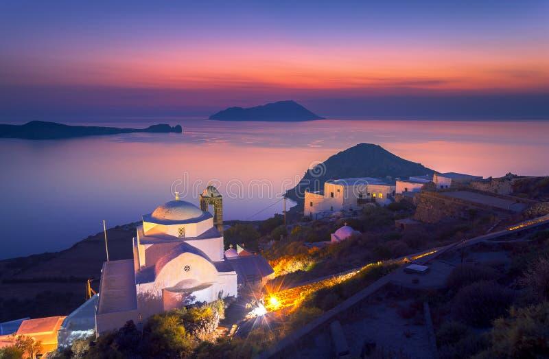 Iglesia de Panagia Thalassitra y opinión del pueblo de Plaka en la puesta del sol, Milos isla, Cícladas foto de archivo