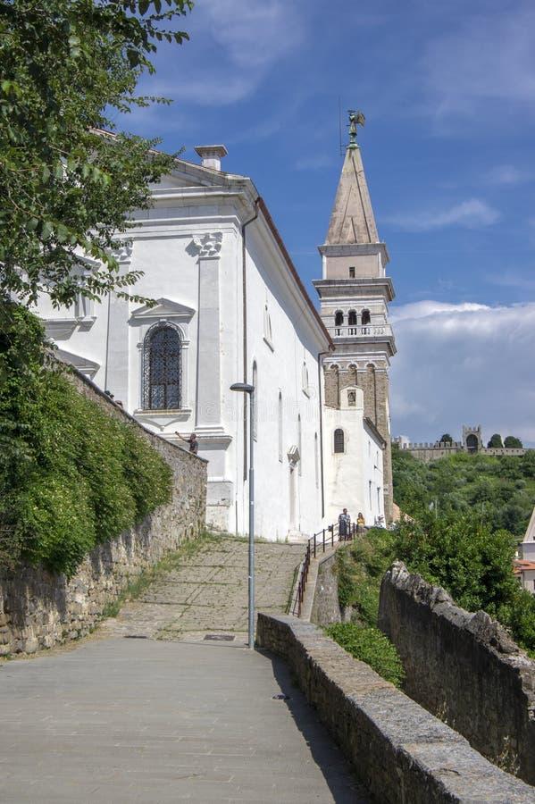 Iglesia de San Jorge en el top de la colina en Piran en Eslovenia, día de verano hermoso con luz del sol y el cielo azul foto de archivo libre de regalías