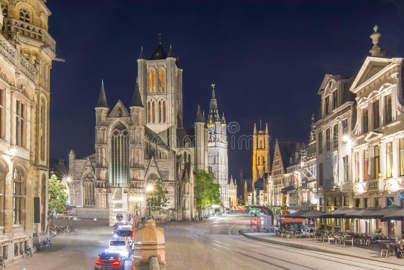 Iglesia de San Nicolás, torre y St Bavo Cathedral en la noche, señor, Bélgica de Belfort fotos de archivo