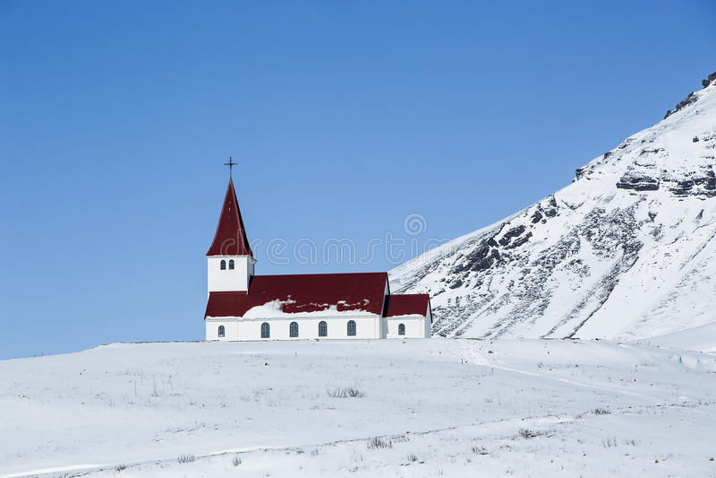 Iglesia de Vik en el invierno con las montañas nevosas, Islandia foto de archivo libre de regalías