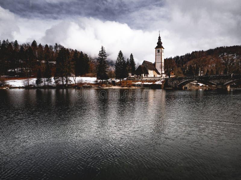 Iglesia del lado del lago con el fondo enselvado fotos de archivo