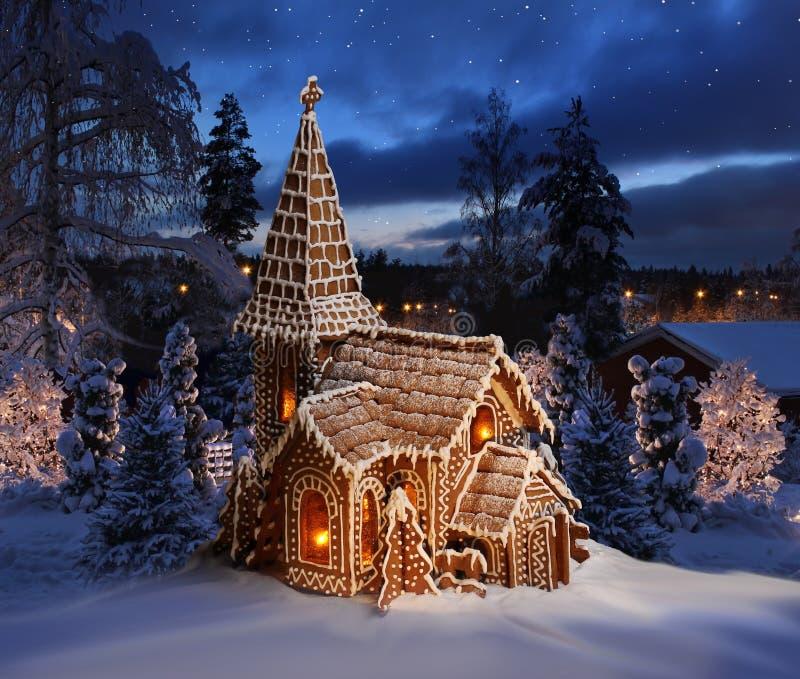 Iglesia del pan de jengibre en paisaje nevoso de la noche de la Navidad foto de archivo