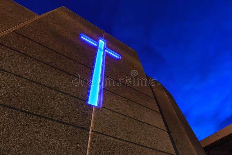 Iglesia en la noche, con la cruz azul iluminada imágenes de archivo libres de regalías