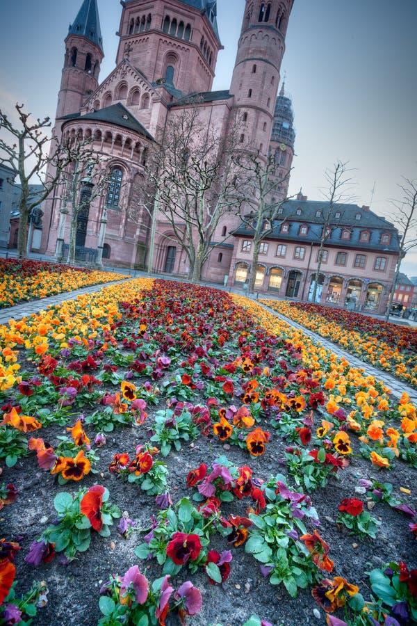 Iglesia europea medieval con el macizo de flores afuera fotografía de archivo libre de regalías
