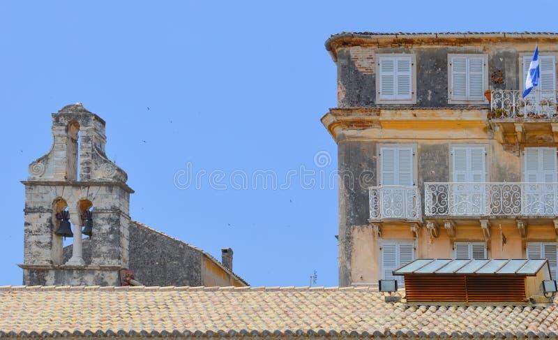 Iglesia griega vieja de sobra y una casa vieja con el wavin griego de la bandera imagenes de archivo