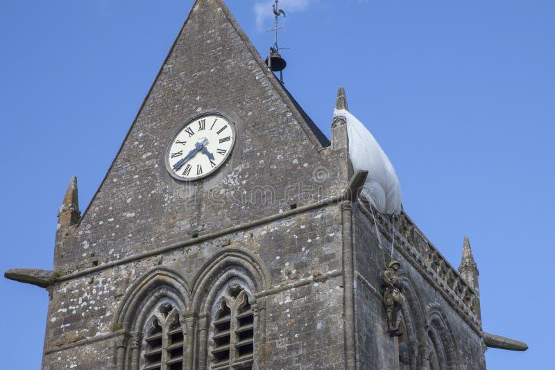 Iglesia histórica de Sainte simple l 'eglise, con un paracaidista colgando en el campanario imagenes de archivo