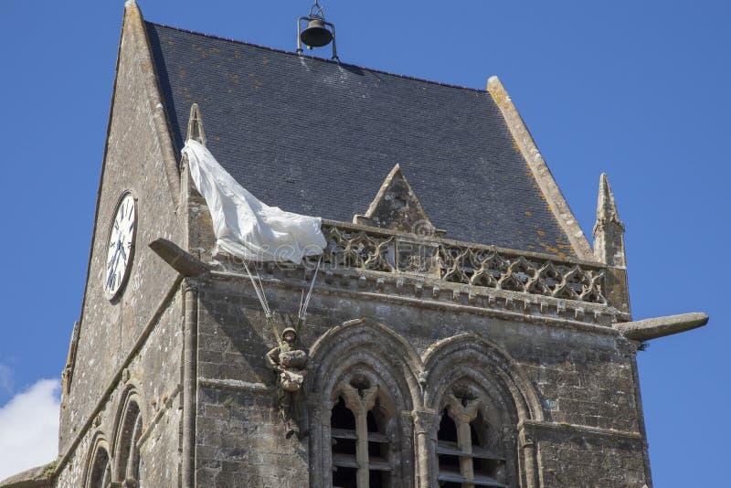 Iglesia histórica de Sainte simple l 'eglise, con un paracaidista colgando en el campanario fotos de archivo libres de regalías