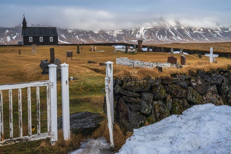 Iglesia negra, Budir, Islandia del oeste - 23 de febrero de 2019: Visión desde la parte trasera en el cementerio y la iglesia ne foto de archivo