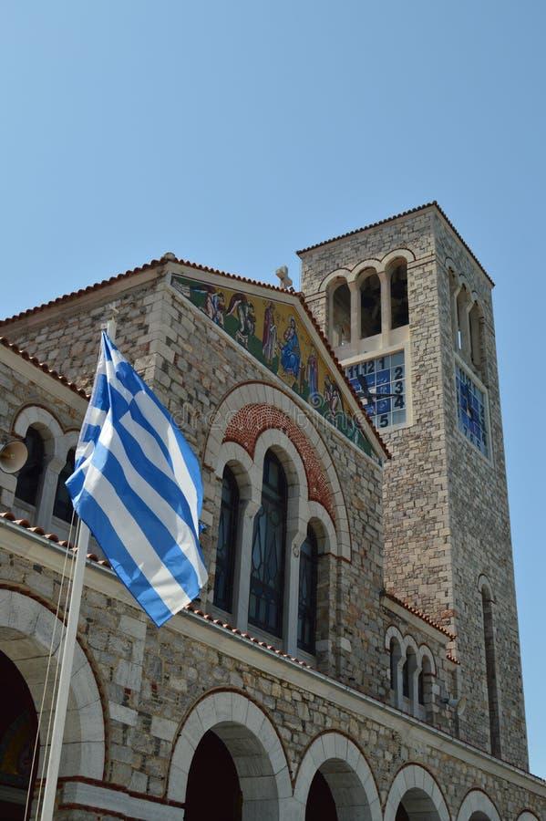 Iglesia ortodoxa de Konstantinos With The Beautiful Blue y de la bandera griega blanca que agitan en el viento Viaje de la histor imagenes de archivo