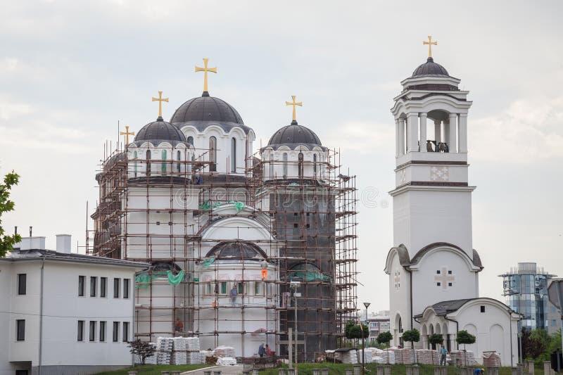 Iglesia ortodoxa de Novi Beograd actualmente en la construcción, con los andamios y los trabajadores, en nueva Belgrado imagen de archivo libre de regalías