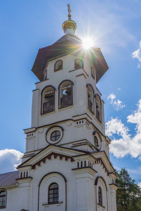 Iglesia a príncipe magnífico Alexander Nevsky del St en Pudozh después de la restauración Campanario ortodoxo contra bosque y azu imagen de archivo
