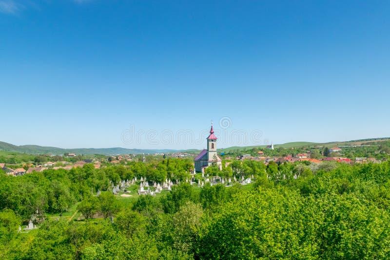 Iglesia rural hermosa con un cementerio en un pequeño pueblo en un día soleado con el cielo azul imagenes de archivo