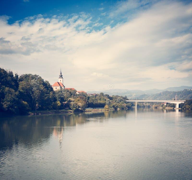 Iglesia vieja en la orilla del río de Drava Maribor, Eslovenia imagenes de archivo