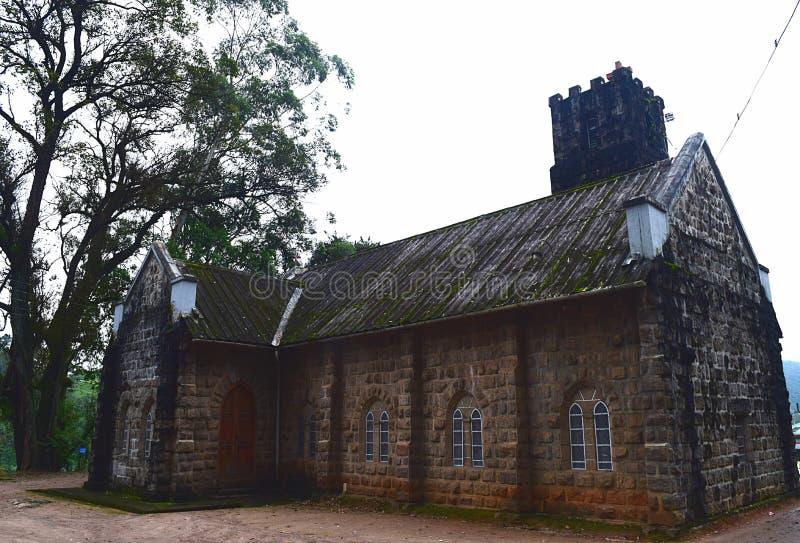 Iglesia vieja histórica hecha de piedras y de un árbol enorme - Muunar, Kerala, la India imagenes de archivo