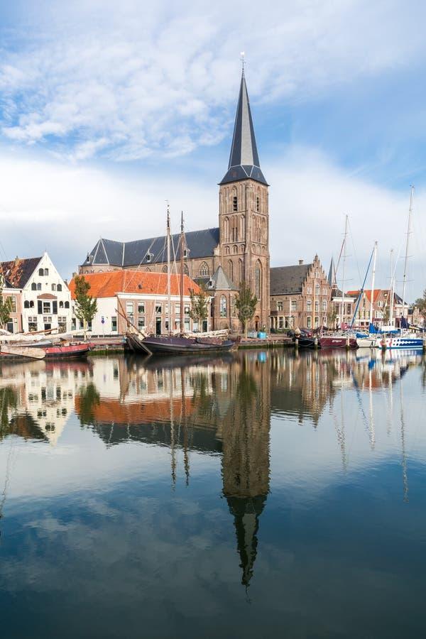 Iglesia y barcos en el canal del sur del puerto de Harlingen, Netherland imagenes de archivo