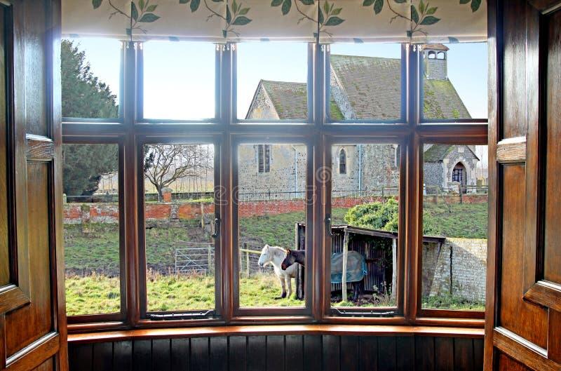 Iglesia y caballos del pueblo de la ventana salediza imagen de archivo libre de regalías