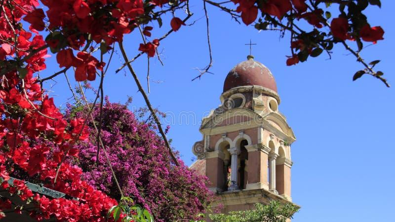Iglesia y campanario viejos con la buganvilla de florecimiento imagen de archivo