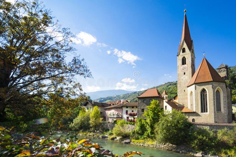 Iglesia y casas a lo largo del río Isarco, Chiusa, Italia imagen de archivo libre de regalías