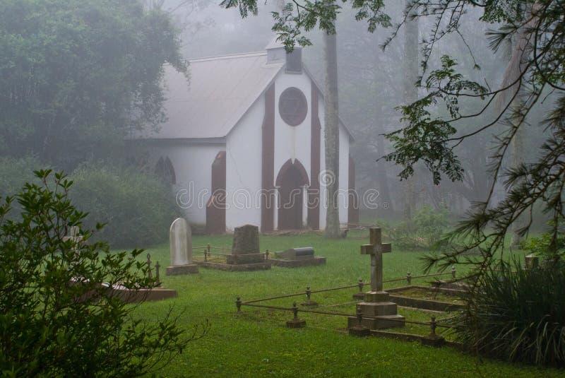 Iglesia y cementerio del país en la niebla imagenes de archivo