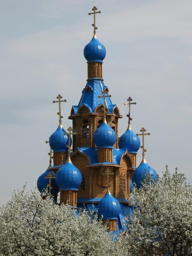 Iglesia y cerezos rusos en flor imagenes de archivo