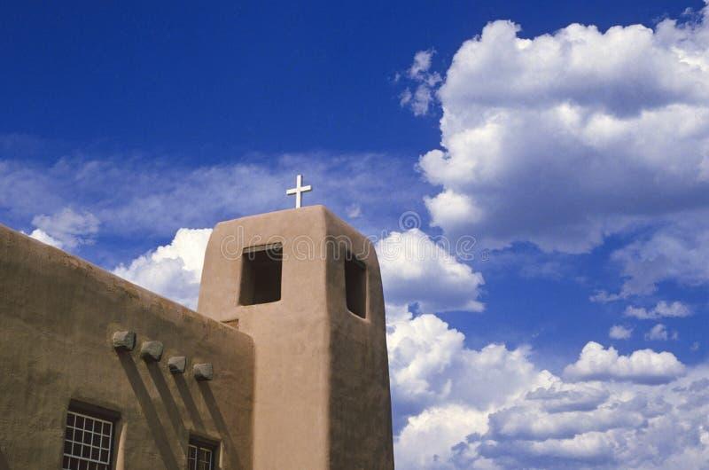 Iglesia y nubes de Adobe foto de archivo