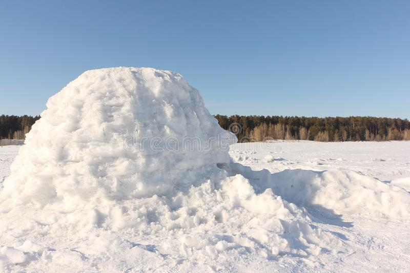 Igloo standing on a snowy glade royalty free stock image