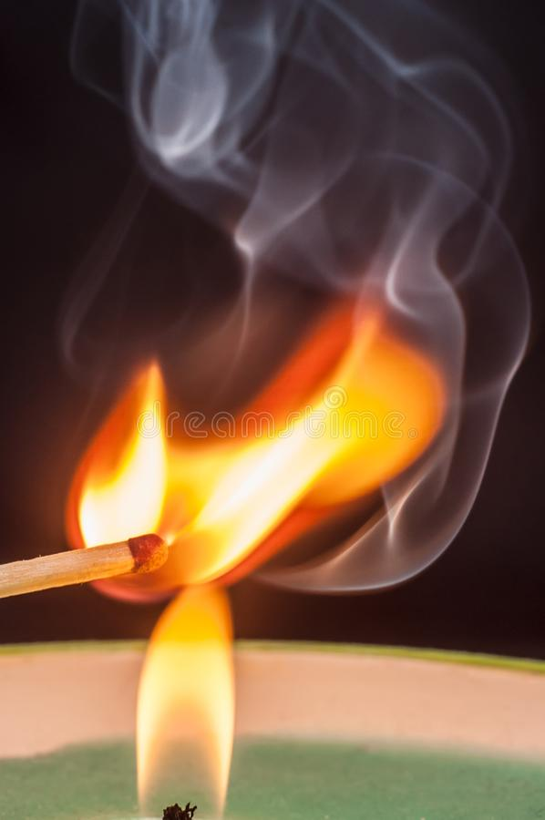 Igniting matches from a candle fire with smoke effectively. Sulfur ignition close up. Macro shooting stock images