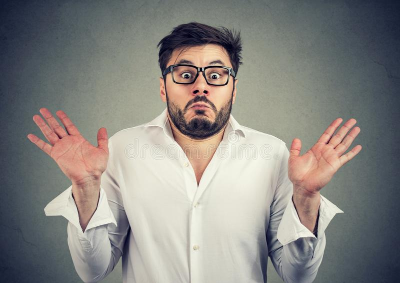 Ignorant man shrugging with shoulders. Young handsome man in eyeglasses looking super confused and shrugging with shoulders looking at camera royalty free stock photo