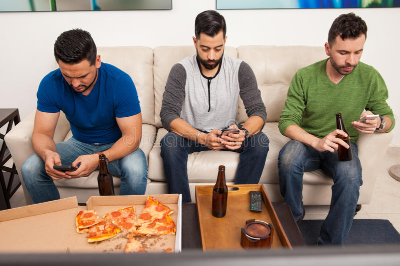 Ignoring each other with smartphones. Portrait of a group of three men hanging out but ignoring each other while using their smartphones royalty free stock image