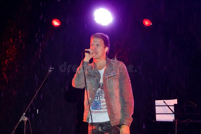 Igor Grohotsky, Ukrainian pop singer sings in the rain at live concert during Street Festival, Vinnytsia, 24.09.2017, editorial. Photo stock images