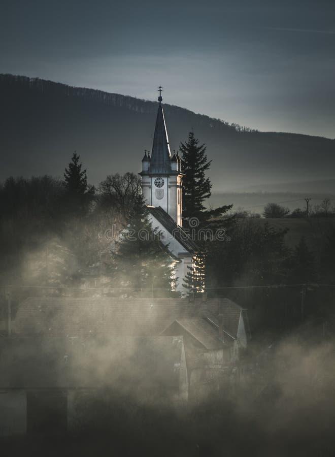 Igreja antiga na vila encoberta na névoa com montanhas e os montes grandes no fundo Foto da igreja branca do prado verde imagens de stock