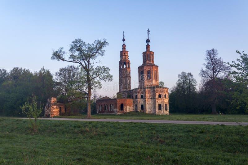 Igreja arruinada velha do século XVIII na vila de Kolentsy, Rússia O sol levanta-se acima das nuvens do mar e do ouro imagem de stock