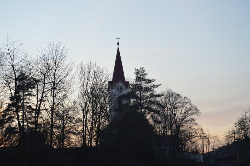 Igreja atrás da floresta após o por do sol foto de stock royalty free