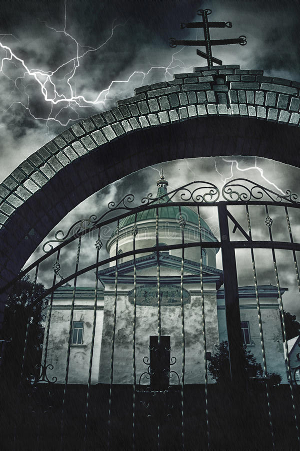 A igreja através de uma arcada do tijolo com uma cruz e uma porta do metal em um fundo do céu noturno tormentoso e do relâmpago fotos de stock royalty free
